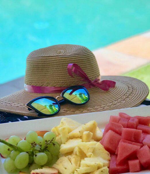 sun hat, platter of freshly cut fruit next to pool