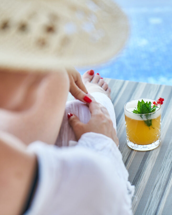 woman sits on chaise lounge next to pool and cocktail