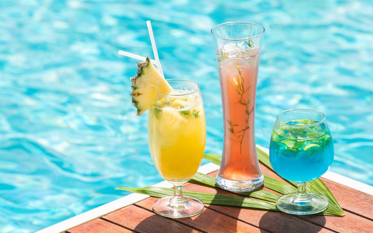 three bright cocktails next to swimming pool